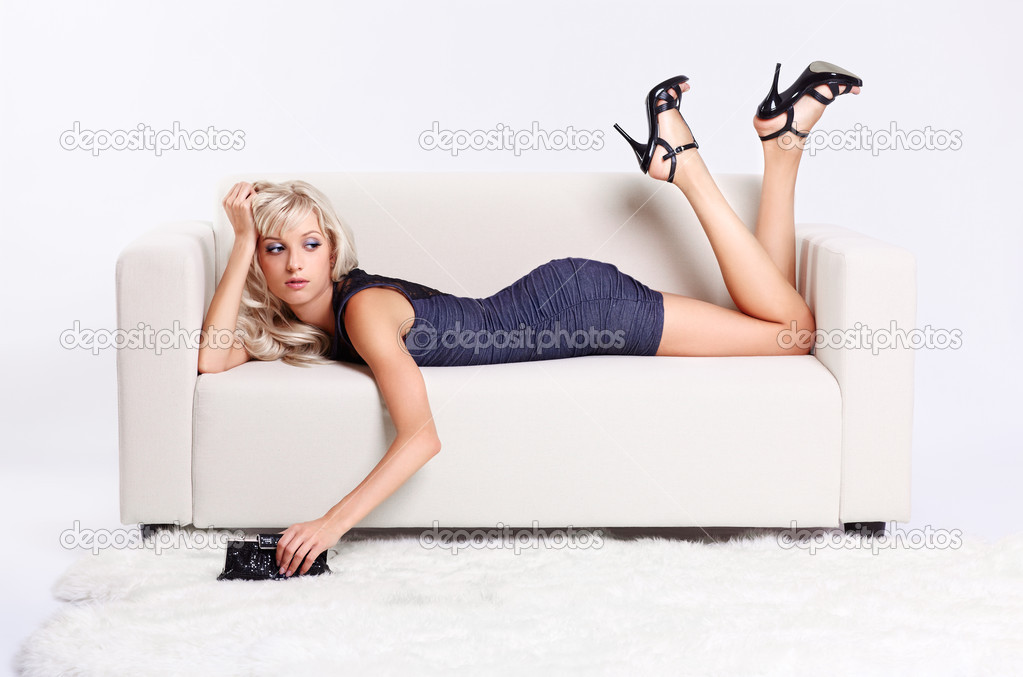 Full-length portrait of beautiful young blond woman on couch with white furs on floor — Stock Photo #6558729