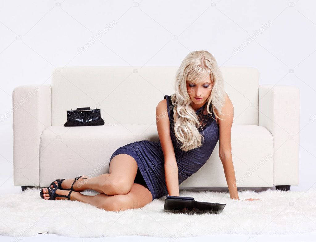 Full-length portrait of beautiful young blond woman sittin on white furs in front of on couch and reading e-book — Stock Photo #6558767