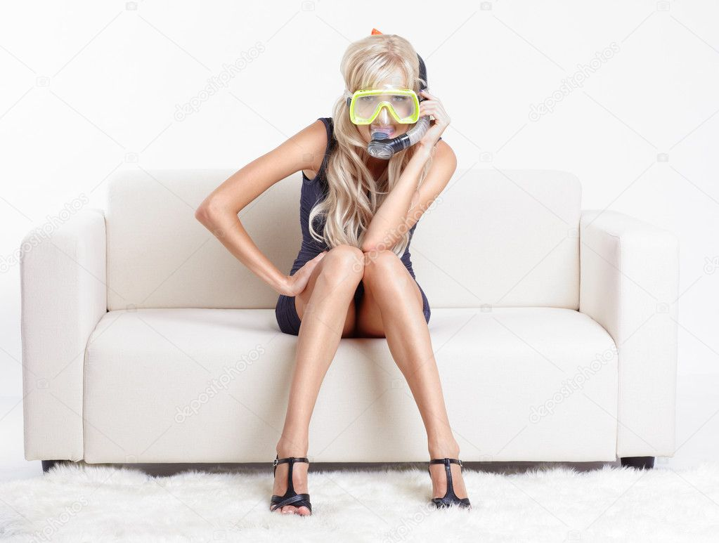 Young blond woman in scuba mask on couch with white furs on floor — Foto Stock #6558828