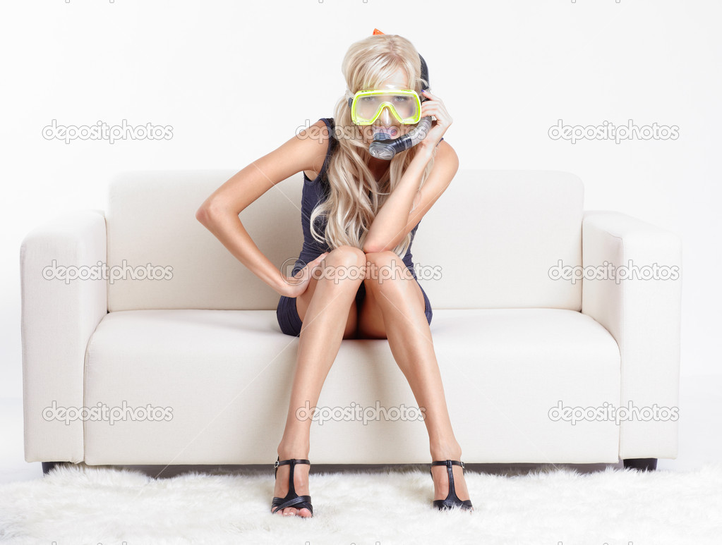 Young blond woman in scuba mask on couch with white furs on floor — Lizenzfreies Foto #6558828