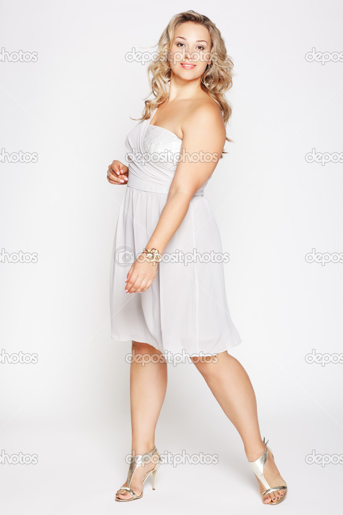 Full-length portrait of beautiful plus size curly young blond woman posing on gray in white dress and court shoes — Stock Photo #6647017