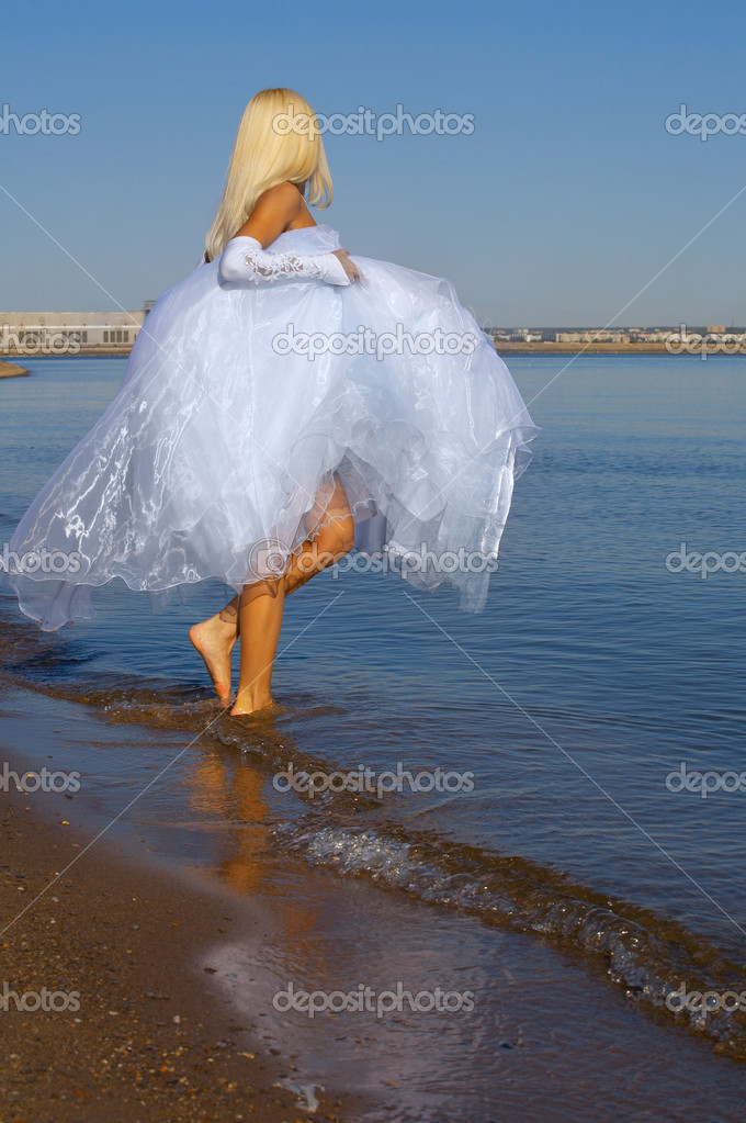 Bride wolking on the beach — Stockfoto #6734487
