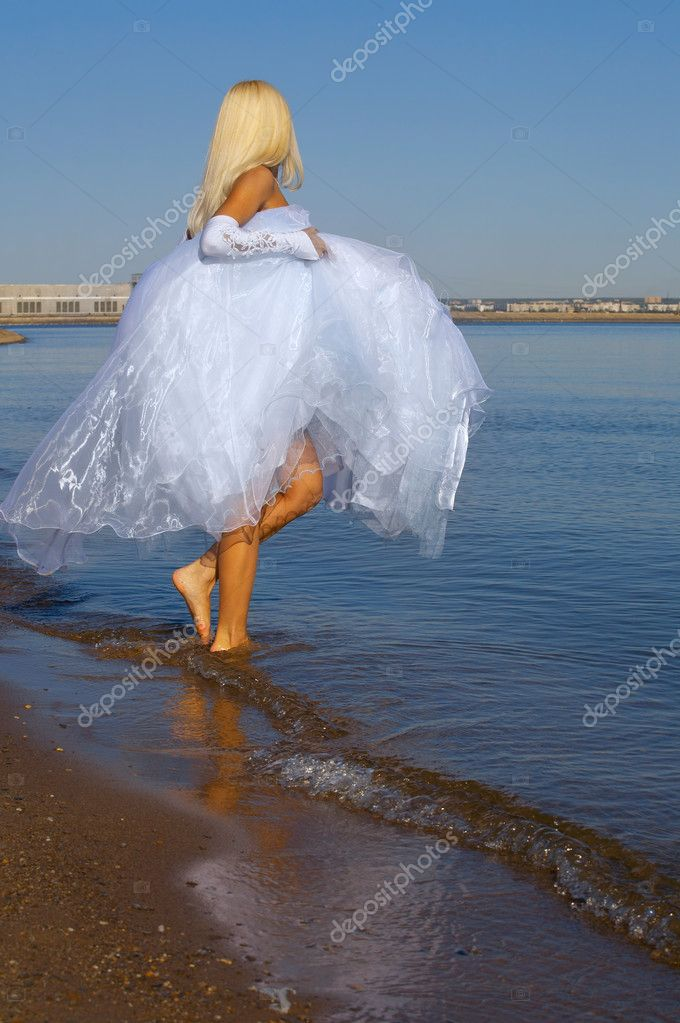 Bride wolking on the beach  Lizenzfreies Foto #6734487