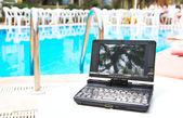 Přenosný počítač poblíž bazén — Stock fotografie