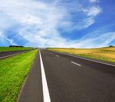 Asfaltové silnici přes modré oblohy — Stock fotografie