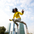 Girl in a yellow blazer jumping — Stock Photo