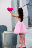 Girl doll in Big City — Stock Photo