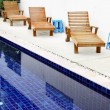 Chaise-longues near pool — Stock Photo