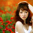 Woman closeup portrait in poppy field — Stock Photo