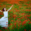 Woman in white dress running poppy field — Stock Photo