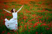Woman in white dress running poppy field — Stock Photo