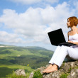 Woman sitting on  edge of a cliff with a laptop — Stock Photo