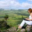 Woman sitting on edge of a cliff with a laptop — Stock Photo #6265590