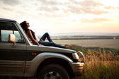 Woman is laying on the car's hood — Stock Photo