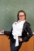 Portrait of attractive female teacher in a classroom — Stock Photo