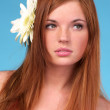 Beautiful young woman with flower in hair — Stock Photo