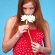 Pretty young woman sniffing white flower — Stock Photo