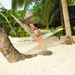 Woman in hammock on beach — ストック写真