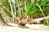 Woman in hammock on beach — Stock Photo