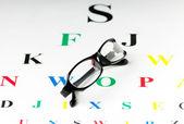 Optical reading glasses on the eyesight table — Stock Photo