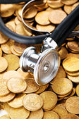 Concept of expensive healthcare with coins and stethoscope — Stock Photo