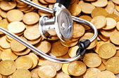 Concept of expensive healthcare with coins and stethoscope — Stok fotoğraf