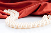 Pearls necklace on satin background — Stockfoto