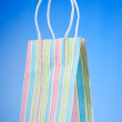 Colourful paper shopping bags against gradient background - Stok fotoğraf