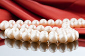 Pearls necklace on satin background — Zdjęcie stockowe