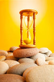 Hourglass on pebbles against gradient — Stock Photo