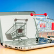 Internet online shopping concept with computer and cart - Stok fotoğraf