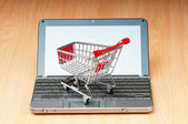 Internet online shopping concept with computer and cart — Стоковое фото
