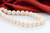 Pearls necklace on satin background — Stock Photo