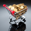Gold coins in shopping cart — Stockfoto