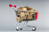 Shopping cart full of coins — Stock Photo