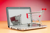 Internet online shopping concept with computer and cart — Zdjęcie stockowe