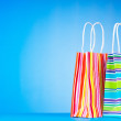 Colourful paper shopping bags against gradient background - Stockfoto