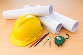 Drawings and hard hat on the desk — Stock Photo
