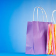 Colourful paper shopping bags against gradient background - Stok fotoraf