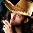 Man in cowbow hat smoking — Stock Photo #6604907