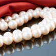 Stock Photo: Pearls necklace on satin background