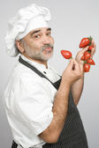 Smiling chef with tomatoes — Stock Photo