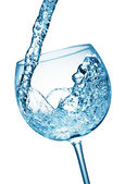 Glass of cool splashing water — Stock Photo