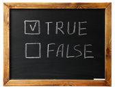 Sant eller falskt på svart krita ombord — Stockfoto