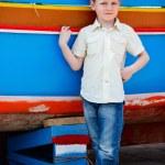 Boy near colorful boat — Stock Photo