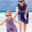 Mother and daughter running at beach — Stock Photo
