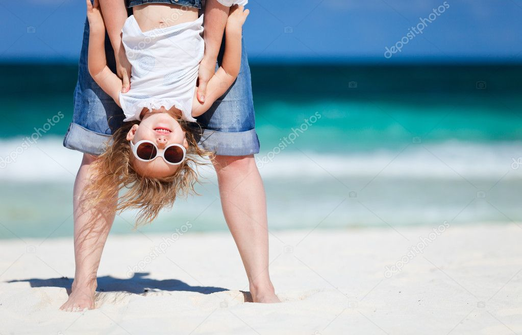 Mother holding her happy smiling daughter upside down having beach fun — Stock Photo #5848209