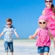 Mother and kids running at beach — Stock Photo