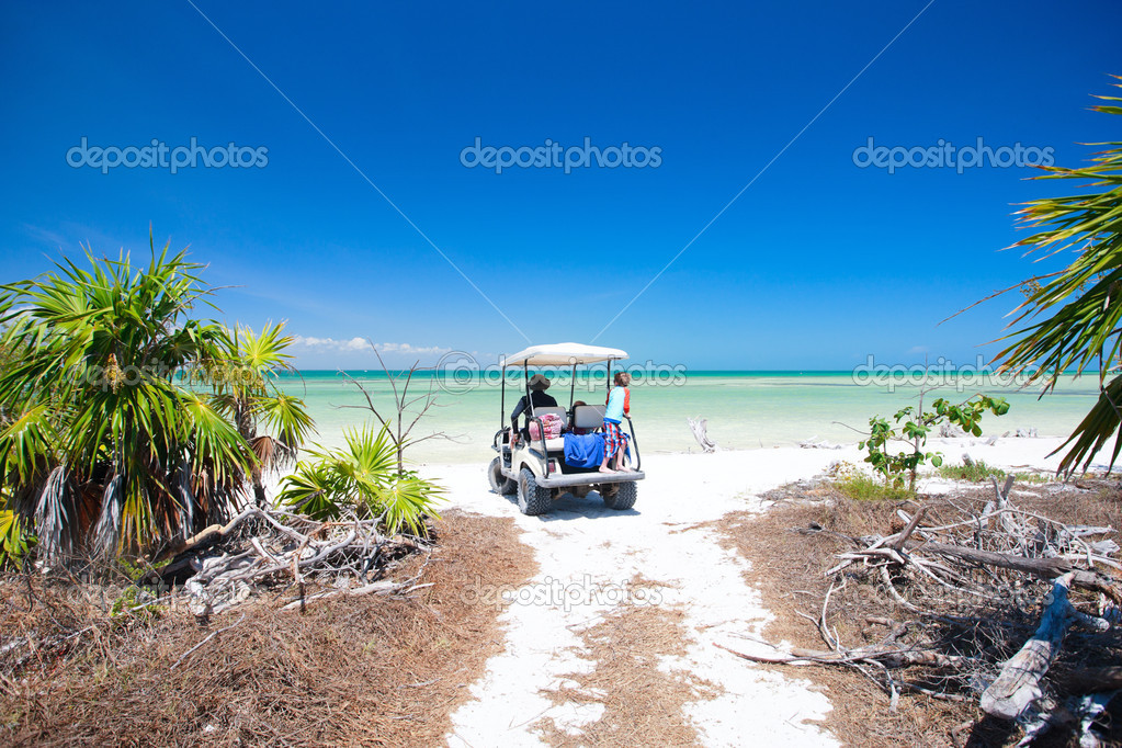 Family driving in golf cart along the tropical beach — Stock Photo #5898823