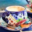 Cappuccino served in colorful cup - Stok fotoğraf